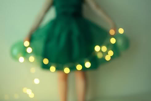 Out of focus woman in green dress with lights
