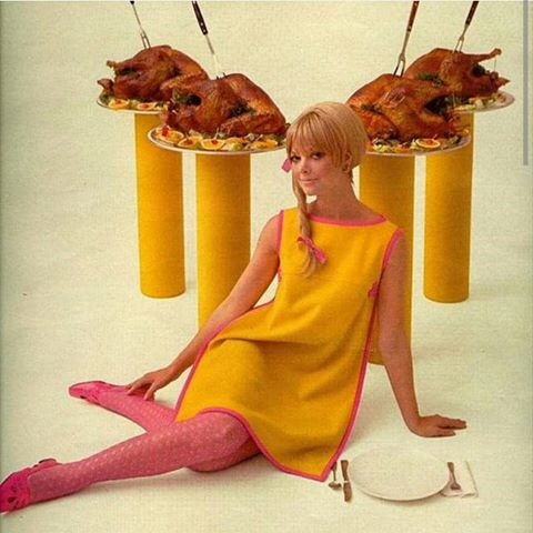 Mod 70's woman in a yellow dress in front of cooked turkey on pedestals.